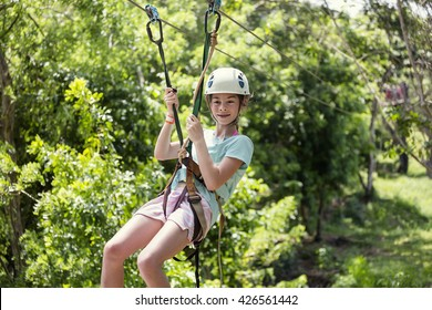 Happy little girl riding a zip line in a lush tropical forest