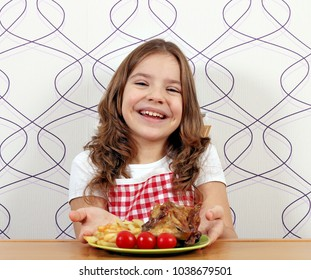 happy little girl with roasted chicken wings on plate