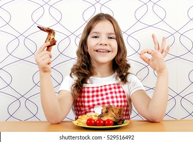 happy little girl with roasted chicken wings and ok hand sign