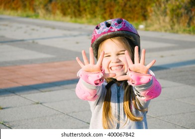 happy little girl roller skating wearing protection and pink helmet waving