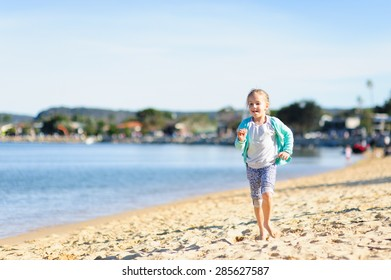 Happy little girl running along the beach on a cool summer day in Australia