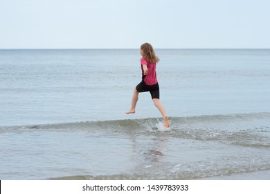 Happy little girl running in Baltic sea and playing with waves