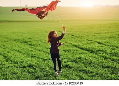 Happy little girl running with kate in hands on the beautiful field.