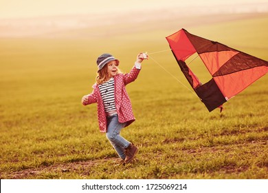 Happy little girl running with kite in hands on the beautiful field at sunrishe time.