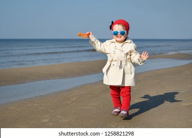 Happy little girl running on Baltic Sea beach in Latvia. Kids play in ocean sand dunes on cold autumn or spring day. Beach fun for family with children