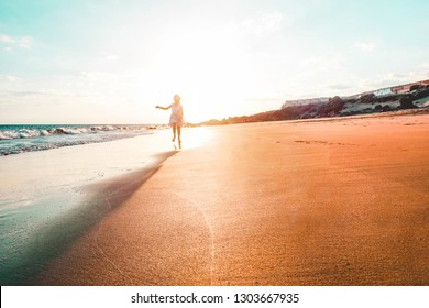 Happy little girl running on tropical beach -  Female chld having fun on vacation holiday - Travel. childhood and wanderlust concept - Focus on silhouette body