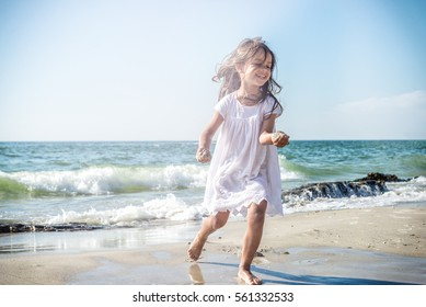 Happy little girl running on the beach