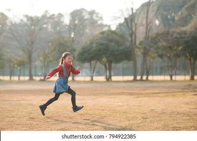 Happy little girl running in the park