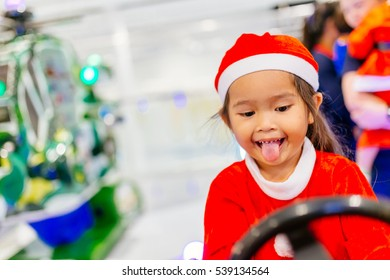 Happy little girl in santa claus costume over christmas. And waiting for gifts from Santa. and playing toy.