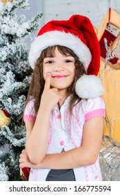 Happy little girl in santa's hat over christmas tree