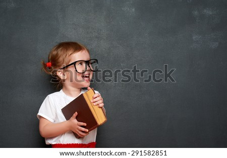 happy little girl schoolgirl with a book from the blackboard