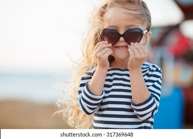 happy little girl at the seaside in the summer.Adorable little girl at beach during summer vacation. Happy baby with sunglasses by the sea