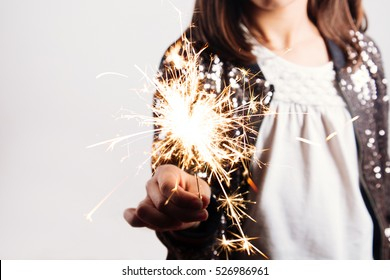 Happy little girl in sequins dress holding a sparkler enjoying the party. Focus on sparkler