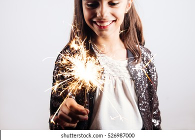 Happy little girl in sequins dress holding a sparkler enjoying the party