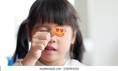 Happy little girl show smilly sticker on finger.