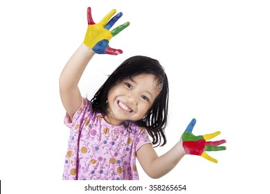Happy little girl showing her hands painted in colorful paints, isolated on white background