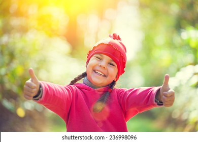 Happy little girl showing thumbs up in sunny day