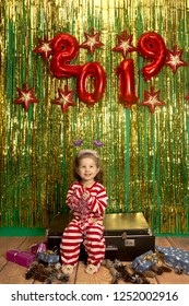 happy little girl sit on retro suitcase christmas tinsel background