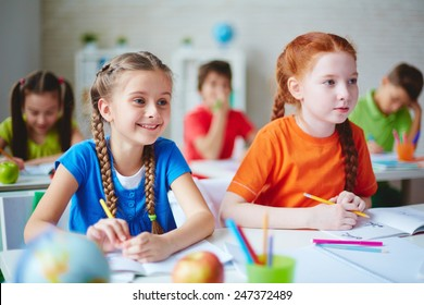 Happy little girl sitting at lesson with her friend near by