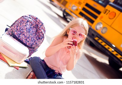 Happy little girl  sitting next to school buses and eating apple. Backback, lunchbox and books next to her. Back to school concept.