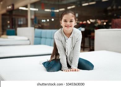 Happy little girl sitting on mattress in mattress store. Choosing mattress in store. Check the softness of the mattress.