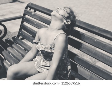 happy little girl sitting on the bench and enjoying the sun