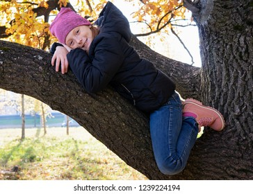 Happy little girl sitting on branch of big tree and smiling on sunny autumn day