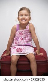 Happy little girl sitting on top of a suitcase