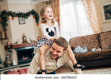 Happy little girl sitting on dad's neck