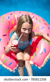 Happy little girl sitting on a colorful inflatable donut with a drink in a  swimming pool.