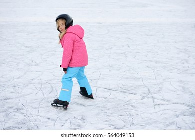Happy little girl skating in winter outdoors, wearing safety helmet