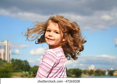 Happy little girl with the sky as background
