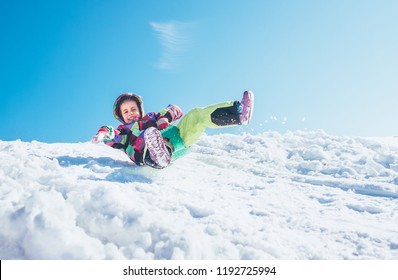 Happy little girl slides down from the snow slope