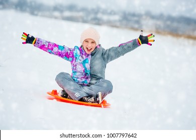 Happy little girl sliding down the hill on saucer sled. Girl enyoing slider ride on the snow