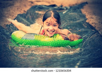 Happy little girl sliding down on water slide. Summer holiday.