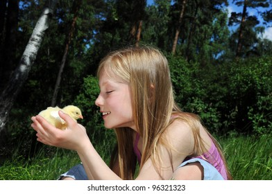 Happy little girl with a small chicken
