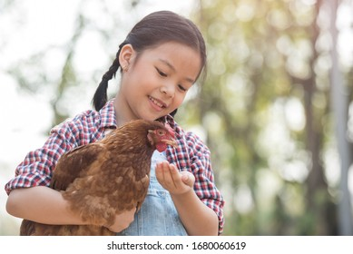 happy little girl with of small chickens sitting outdoor. portrait of an adorable little girl, preschool or school age, happy child holding a fluffy baby chicken with both hands and smiling.