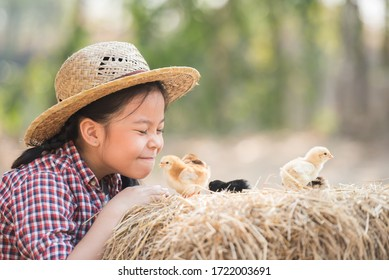 happy little girl with of small chickens sitting outdoor. portrait of an adorable little girl, preschool or school age, happy child holding a fluffy baby chicks with both hands and smiling.