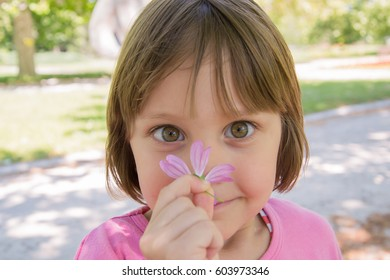 Happy little girl smelling flower