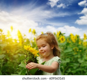 Happy little girl smelling a sunflower on the field .