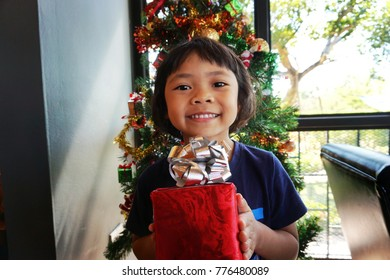 Happy little girl smiles with Christmas gift box.