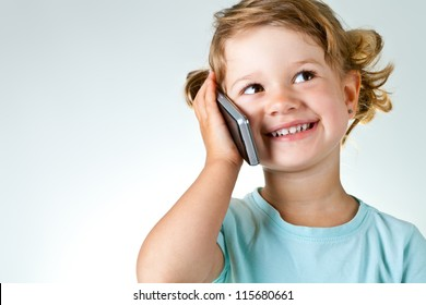 Happy little girl speaking by cell phone against light gray-blue background with copy space