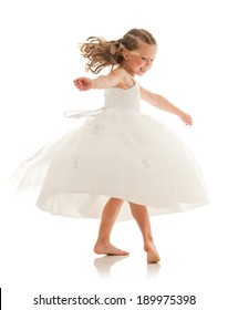 Happy little girl spinning fast in white flower girl dress, causing it to flare out. Studio shot on white background with reflection.