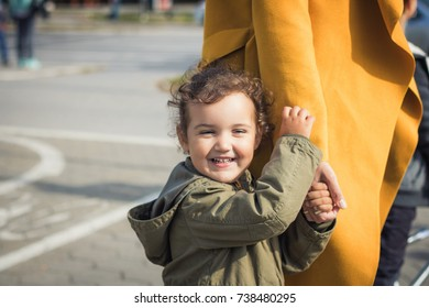 Happy little girl standing close to her mother and holding hands. Cute daughter holding hands with mother and having fun in the city.