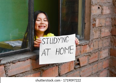 """Happy little girl standing near the window and holding a sheet of paper that says """"STUDYING AT HOME"""". Focus is on the paper."""