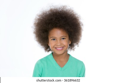 happy little girl standing on a white background and looking at the camera