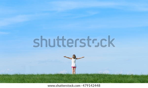 happy little girl standing on a mountain with blue sky background