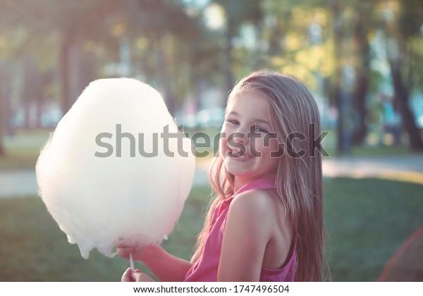 夏の公園に甘い綿菓子を持つ幸せな少女