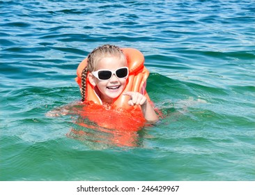 Happy little girl swimming with life jacket in the sea