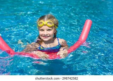 Happy little girl swimming with a pink foam noodle in a pool while on summer vacation